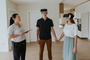 Estate agent with young couple wearing VR headsets in new apartment